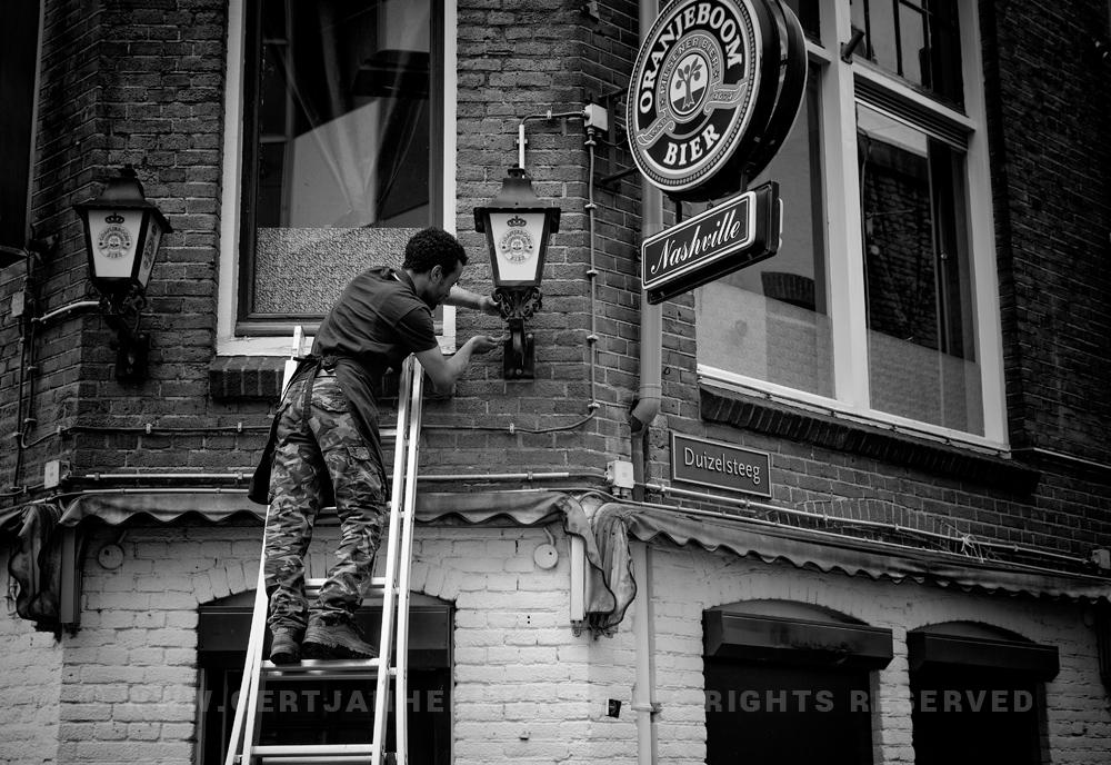 straatfotografie man op een ladder