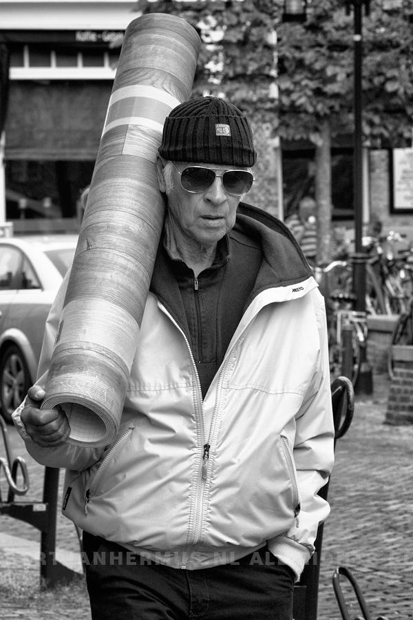 straatfotografie man met rol linoleum Friesland