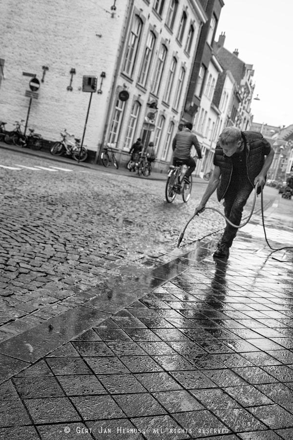 straatfotografie man maakt straat schoon