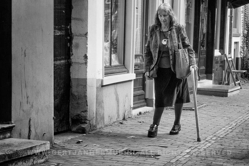 straatfotografie vrouw met stok