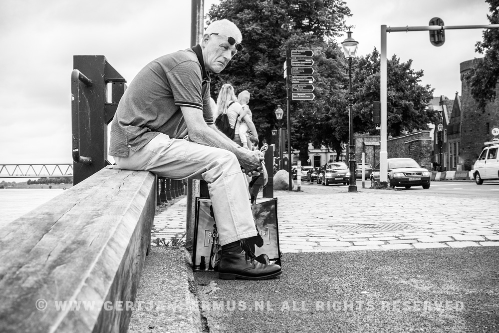 straatfotografie man op muurtje